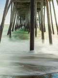 Misty Waves under Wooden Pier. Timed exposure creates an ethereal look of the waves coming in and out underneath a wooden pier Royalty Free Stock Photography