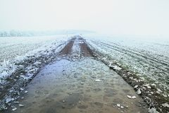 Winter frozen field road with cracked ice. Misty winter landscape with snowy field and frozen road Stock Image