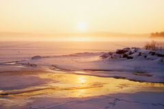 Misty winter sunrise over a frozen lake Royalty Free Stock Photography