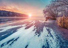 Misty winter sunset on the frozen pond in the city park. Royalty Free Stock Photo