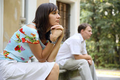 Misunderstanding. Young sad woman and man sitting on marble steps in park, selective focus Stock Photo