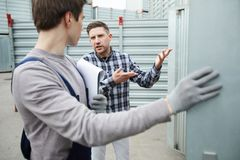 Misunderstanding client talking to storage worker stock photography