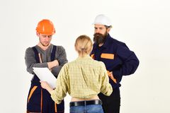 Misunderstanding concept. Brigade of workers, builders in helmets, repairers, lady arguing, discussing contract, white. Background. Woman amend plan of repair royalty free stock images