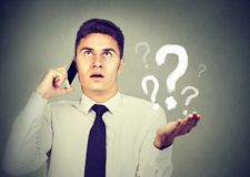 Misunderstanding and distant call concept. Upset annoyed man talking on mobile phone has many questions. stock photos