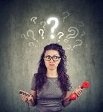 Upset worried confused woman with telephone has many questions. Misunderstanding and distant call. Upset worried confused woman talking on a phone has many Royalty Free Stock Image