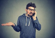 Upset young man talking on cellphone feeling annoyed and frustrated. Misunderstanding and distant phone call. Upset young man talking on cellphone feeling royalty free stock images