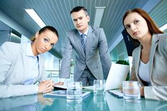 Misunderstanding. Serious boss with his two employees looking at camera with displeasure Royalty Free Stock Image