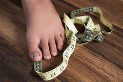 Misura del ragazzo i suoi piedi facendo uso del nastro di misurazione Fotografia Stock