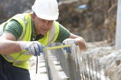 Misura della holding dell'operaio di costruzione Fotografia Stock