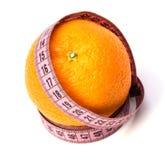 Misura di nastro avvolta intorno all'arancio Immagini Stock Libere da Diritti