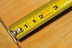 Misura di nastro gialla che misura una parte di legno Fotografie Stock Libere da Diritti