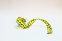 Misura di nastro gialla in metri e pollici in una spirale Fotografia Stock Libera da Diritti