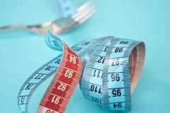 Misura di nastro intorno ad una forcella come concetto per la dieta La forcella è avvolta in nastro di misurazione blu su fondo b fotografia stock