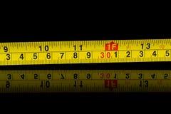 Misura di nastro nei millimetri e nei pollici sul nero Immagine Stock