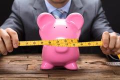 Misura di nastro di Squeezing Piggybank With dell'uomo d'affari sulla Tabella fotografia stock libera da diritti