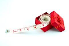 Misura di nastro in un contenitore di regalo rosso Immagine Stock Libera da Diritti