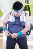 Misura di peso eccessivo dell'uomo la sua pancia alla palestra Fotografia Stock