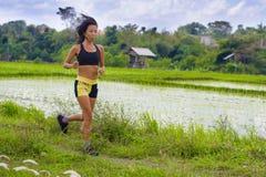 Misura e donna tailandese asiatica sportiva con l'ente atletico che si prepara all'aperto nell'allenamento corrente duro sul paes Immagine Stock