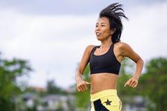 Misura e donna tailandese asiatica sportiva con l'ente atletico che si prepara all'aperto nell'allenamento corrente duro sul paes Immagini Stock Libere da Diritti