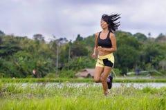 Misura e donna tailandese asiatica sportiva con l'ente atletico che si prepara all'aperto nell'allenamento corrente duro sul paes Fotografia Stock