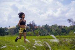 Misura e donna tailandese asiatica sportiva con l'ente atletico che si prepara all'aperto nell'allenamento corrente duro sul paes Fotografie Stock Libere da Diritti