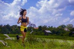 Misura e donna tailandese asiatica sportiva con l'ente atletico che si prepara all'aperto nell'allenamento corrente duro sul paes Fotografia Stock Libera da Diritti