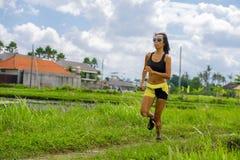 Misura e donna tailandese asiatica sportiva con l'ente atletico che si prepara all'aperto nell'allenamento corrente duro sul paes Fotografie Stock