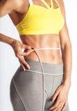 Misurando un certi forte ABS della donna e pancia piana isolati fotografie stock libere da diritti