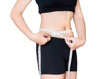 Misurazione del giro vita di un modello della donna nel fondo bianco Fotografia Stock