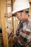Misurazione dell'operaio di costruzione Fotografia Stock Libera da Diritti