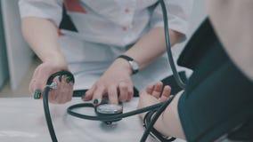 Misurazione di pressione sanguigna Il dottore e paziente Ritardi e braccia video d archivio