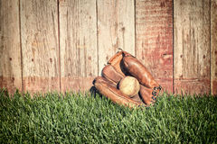 Mitón y bola viejos de béisbol en hierba contra la cerca de madera Fotos de archivo