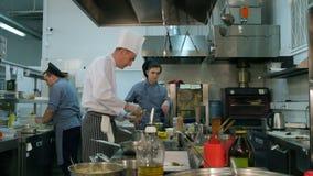 Mit Butter bestreichendes Brot des Chefs vor dem Rösten und der Unterhaltung mit Kochauszubildendem stock video footage