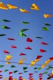 Mit dem Kopfe stoßen, bunte Parteiflaggen, auf einem blauen Himmel Stockbilder