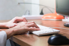 Mit der PC-Frau zu Hause arbeiten, die ein Blog schreibt Weibliche Hände auf Th Lizenzfreie Stockfotografie