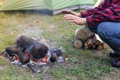 Mit einem Feuer im Holz im Wald kampieren Stockfotos