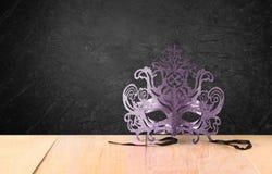 Mit Filigran geschmückte mysteriöse venetianische Maskerademaske auf Holztisch und schwarzem Hintergrund der Beschaffenheit Lizenzfreies Stockbild