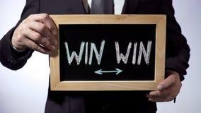Mit Gewinn für beide Parteien geschrieben auf Tafel, Geschäftsmann, der Zeichen, Geschäftskonzept hält stockfotografie