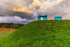 Mit Gras bedeckter Hügel mit zwei Gegenständen Lizenzfreie Stockfotos