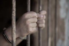Mit Handschellen gefesselte Hände eines Gefangenen im Gefängnis, männliche Gefangene wurden streng im dunklen Gefängnis, Gewalttä stockbilder