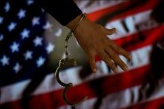 Mit Handschellen gefesselte Hand vor der Landesflagge Übergeben Sie das Anhalten einer Pistole vor Backsteinmauer mit rauem Schat stockfotos