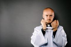 Mit Handschellen gefesselter katholischer Priester stockbilder