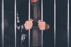 Mit Handschellen gefesselter Mann hinter Gefängnisstangen Stockbilder