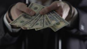 Mit Handschellen gefesselter Oligarch, der hinter Gefängnisstangen steht und Geld, Bestechungsgeldangebot hält stock video