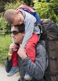 Mit Kind wandern, tragendes schlafendes Kind des Vaters Stockbild