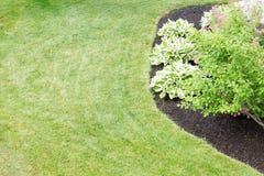 Mit Laub bedecktes Blumenbeet in einem ordentlich manikürten grünen Rasen Stockbild
