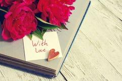 Mit Liebe Blumenstrauß von rosa Pfingstrosen, von einem dekorativen Herzen, von altem Fotoalbum und von weißen Karte mit der Aufs Stockfoto