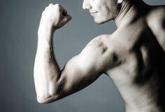Mit nacktem Oberkörper Mann, der seinen zweiköpfigen Muskel zeigt Lizenzfreie Stockfotos