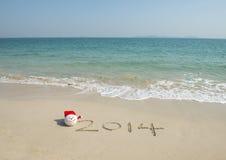 2014 mit Sankt-Hut auf Seestrandsand Lizenzfreies Stockbild