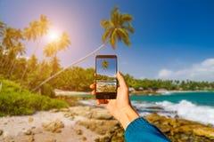 Mit Smartphone in der Hand fotografieren kleines Auto auf Dublin-Stadtkarte Sonnenuntergang auf einem tropischen Strand Lizenzfreie Stockbilder